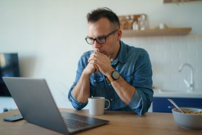 man sitting at laptop contemplating what not to include in a will